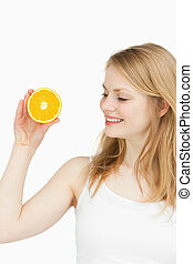 Joyful woman holding an orange against white background