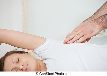 Peaceful patient being massaged by a doctor in a room