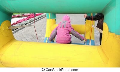 Girl walk in inflated wheel in park at autumn day at Bolotnaya square