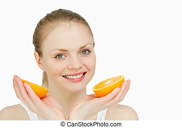 Smiling woman holding oranges against white background