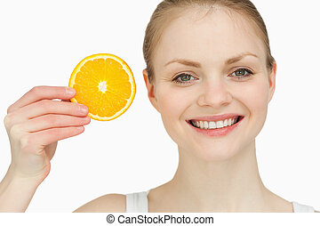 Cheerful woman holding a slice of orange against white...