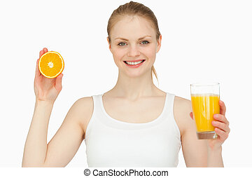 Woman holding a glass while presenting an orange against...