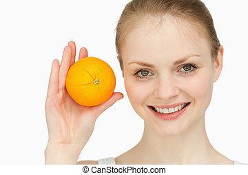 Joyful blonde-haired presenting an orange against white...
