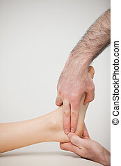 Two fingers pressing the Achilles tendon of a patient in a...
