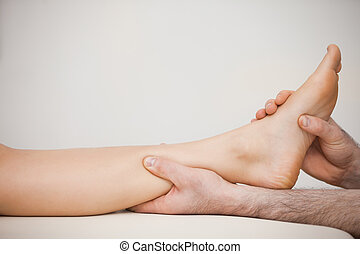 Chiropodist holding the calf of a patient in his medical...