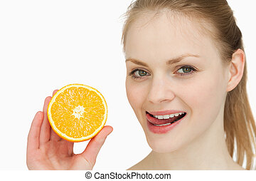 Woman holding an orange while placing her tongue on her lips...