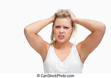 Upset woman standing while placing her hands on her head
