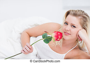 Young woman holding a pink rose while lying on her bed