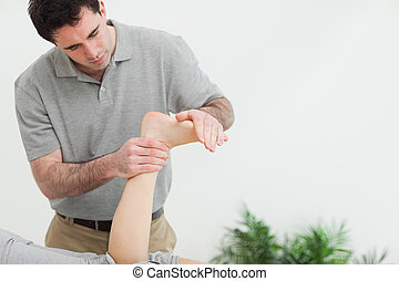 Brown-haired therapist stretching the foot of a patient in a...