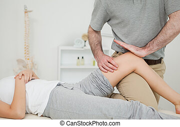 Serious osteopath massaging the knee of a patient in a room