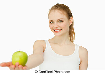 Woman smiling while holding an apple