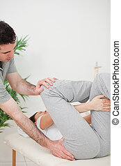 Close-up of a physiotherapist helping a woman for her...