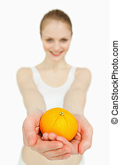 Close up of a woman presenting a tangerine against white...