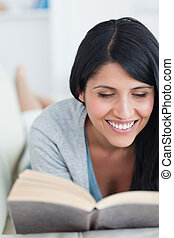 Woman smiling while reading a book as she lies on a couch