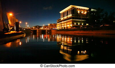 boat moves along Moscow River at night, on embankment drive...