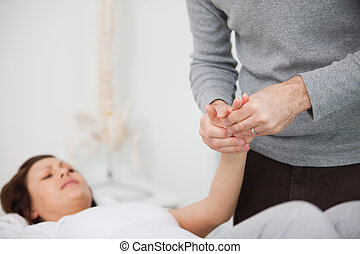 Physiotherapist massaging a painful hand indoors