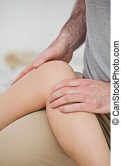 Physiotherapist folding a leg over her thigh