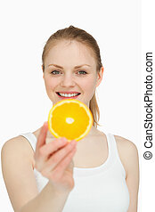 Smiling woman presenting a slice of orange against white...