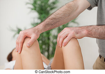 Knees of a patient being held by a doctor in a room