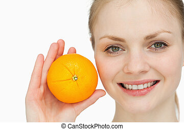 fair-haired woman holding an orange against white background