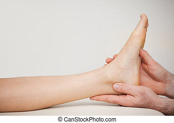 Chiropodist holding the foot of a patient in a medical room