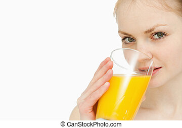 Young woman drinking a glass of orange juice against white...