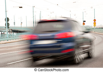 Small blue car in blurred motion on bridge