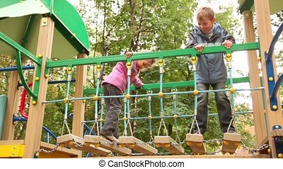 Little girl and boy rock on hang down steps at playground at...