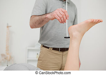 Doctor checking the reflexes of a patient in a room