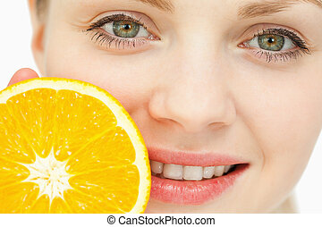 Close up of a woman placing an orange near her lips against...