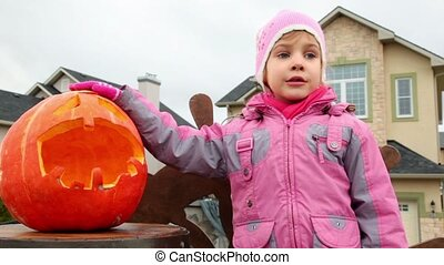 Little girl chewes candy, pumpkin of Halloween at backround...
