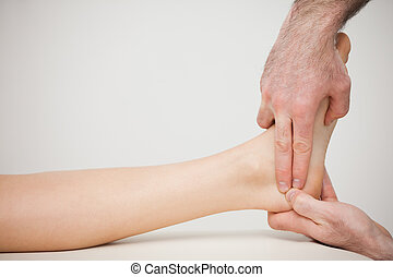 Chiropodist placing two fingers on a foot