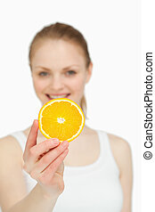 Woman presenting an orange slice while smiling against white...