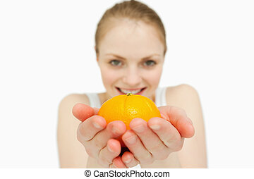 Young woman holding a tangerine against white background
