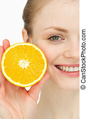 Close up of a smiling woman holding an orange against white...