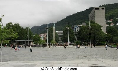 People pass through plaza in Norwegian town, overview, time...