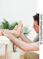 Close up of a physiotherapist massaging a foot in a room