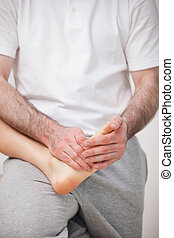 Podiatrist manipulating the foot of a woman while holding it on his thigh indoors