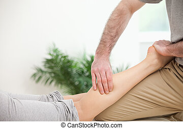 Physiotherapist pressing a leg with his fingers