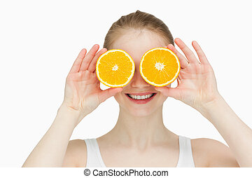 Smiling woman placing oranges on her eyes against white...