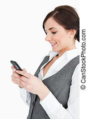 Attractive businesswoman text-messaging against white...