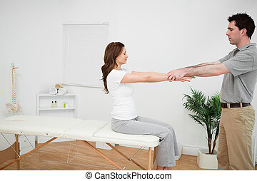 Manual stretching being made by a doctor in a medical room