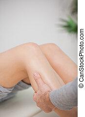 Close up of a masseur massaging a calf