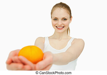 Joyful woman presenting a tangerine against white background