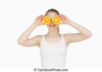 Blond-haired woman placing oranges on her eyes against white...