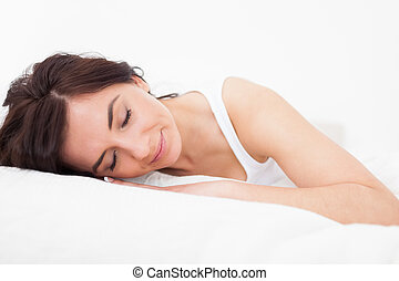 Brunette woman falling asleep in her bed