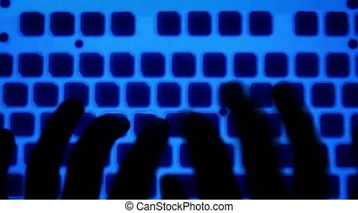 Dark fingers type on keyboard with blue backlight and orange...