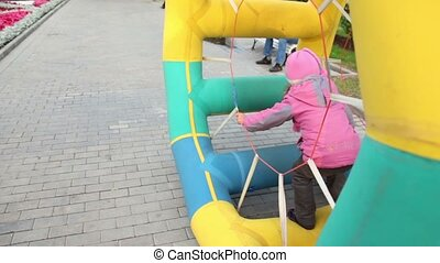Girl walk in inflated wheel in park at autumn day at...