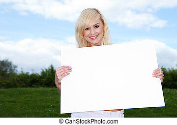 Blonde woman holding empty sign outside