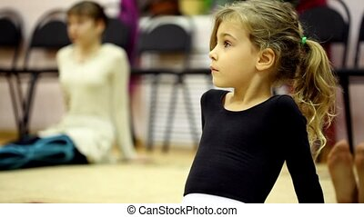 Little girl dressed in ballet clothes sit on floor